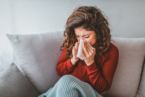 Portrait of woman with allergy blowing her nose