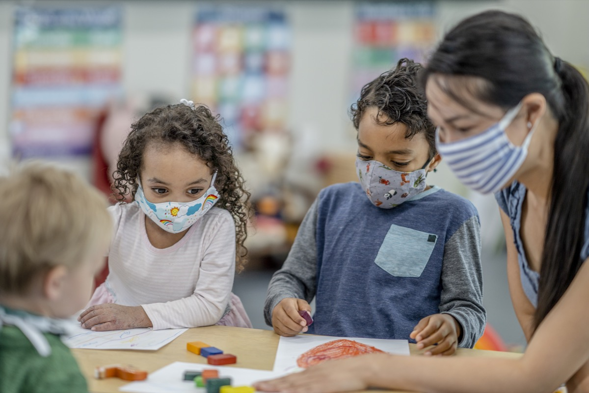 group of children colouring at a table while wearing protective face masks to avoid the transfer of germs.