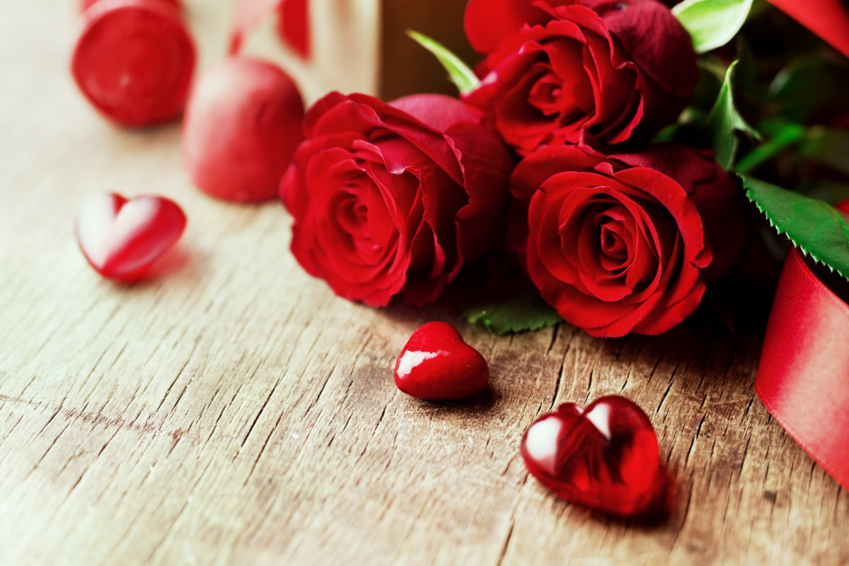 Rose bouquet and hearts on a wooden baord