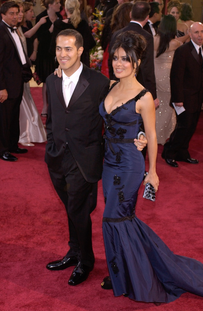 salma hayek in a blue gown standing next to her brother sammy on a red carpet