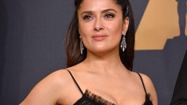 salma hayek wearing a black dress and long earrings on a red carpet