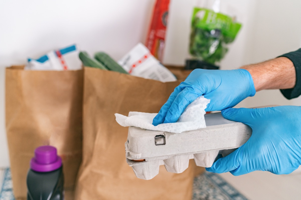 Person sanitizing grocery packages