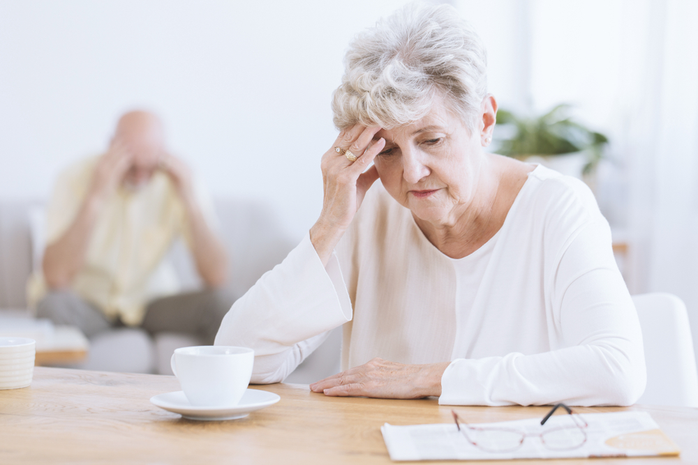 A senior woman sits at a table in front of a coffee while holding her head with a distressed look on her face