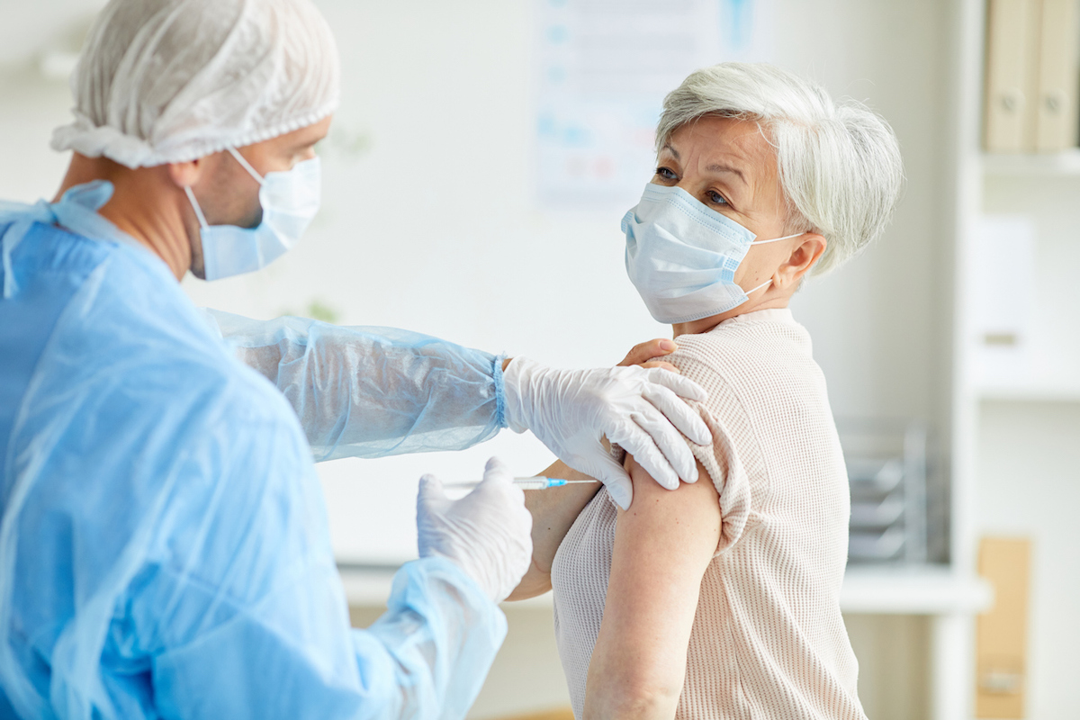 General practitioner wearing protective uniform giving injection with coronavirus vaccine to senior woman