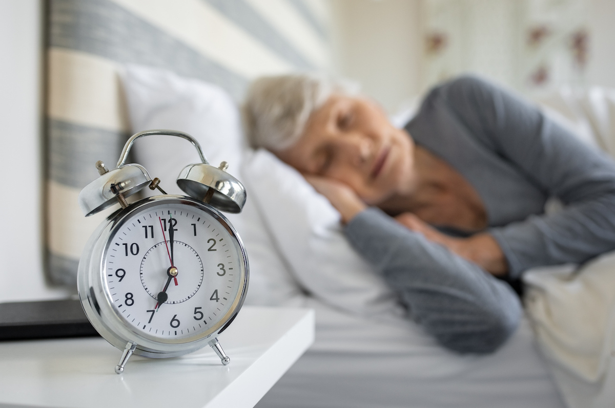 Closeup of alarm clock with senior woman in deep sleep in background