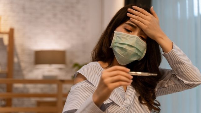 Portrait of woman suffering high temperature and common cold in bedroom. Fever, high temperature, common cold, migraine, tiredness, covid 19 symptoms