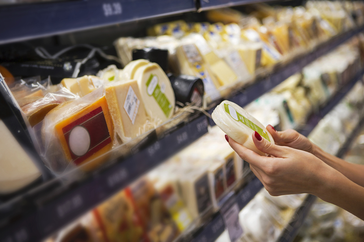 Woman buying cheese in a supermarket