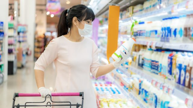 Woman with hygienic mask and rubber gloves with shopping cart in grocery store looking for daily fresh milk to buy during covid-19 outbreak for preparation for a pandemic quarantine