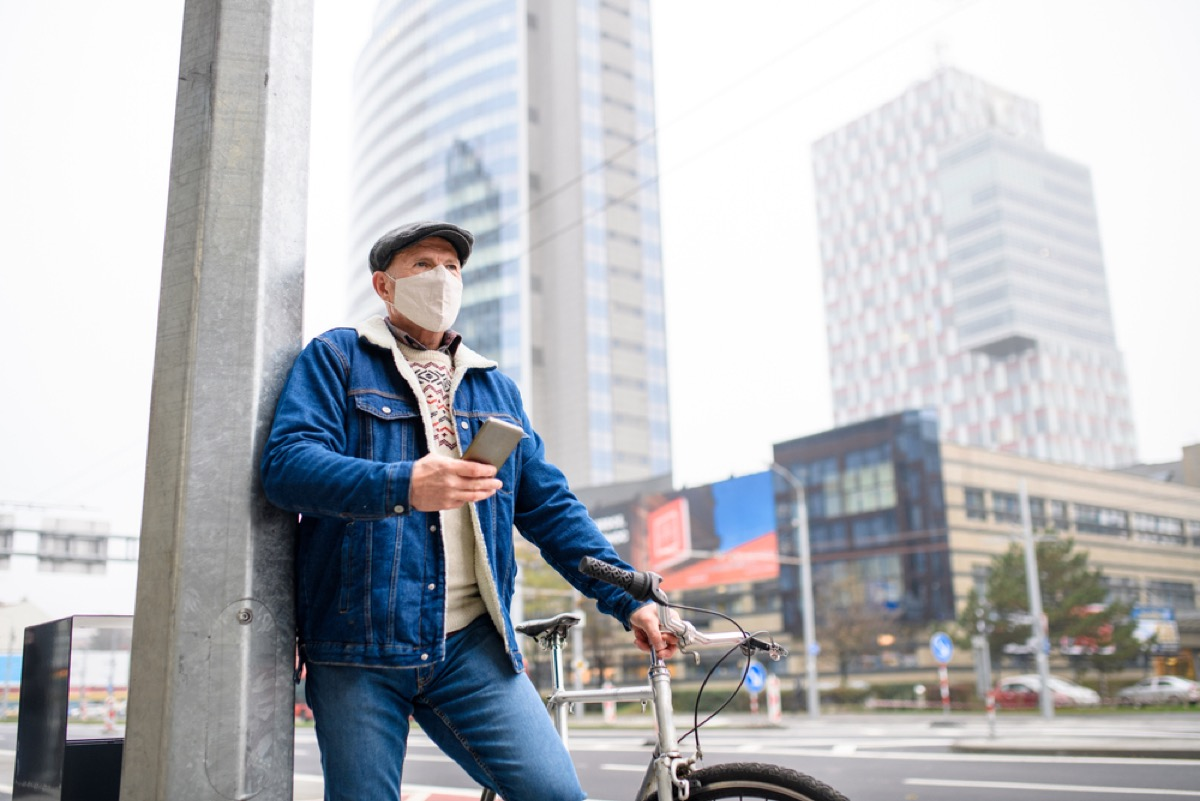 older man with face mask and phone standing next to his bike outside