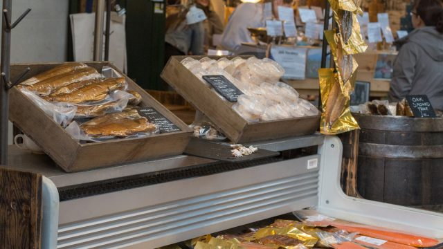 A market stall selling smoked fish in Borough Market, London, with people in the background