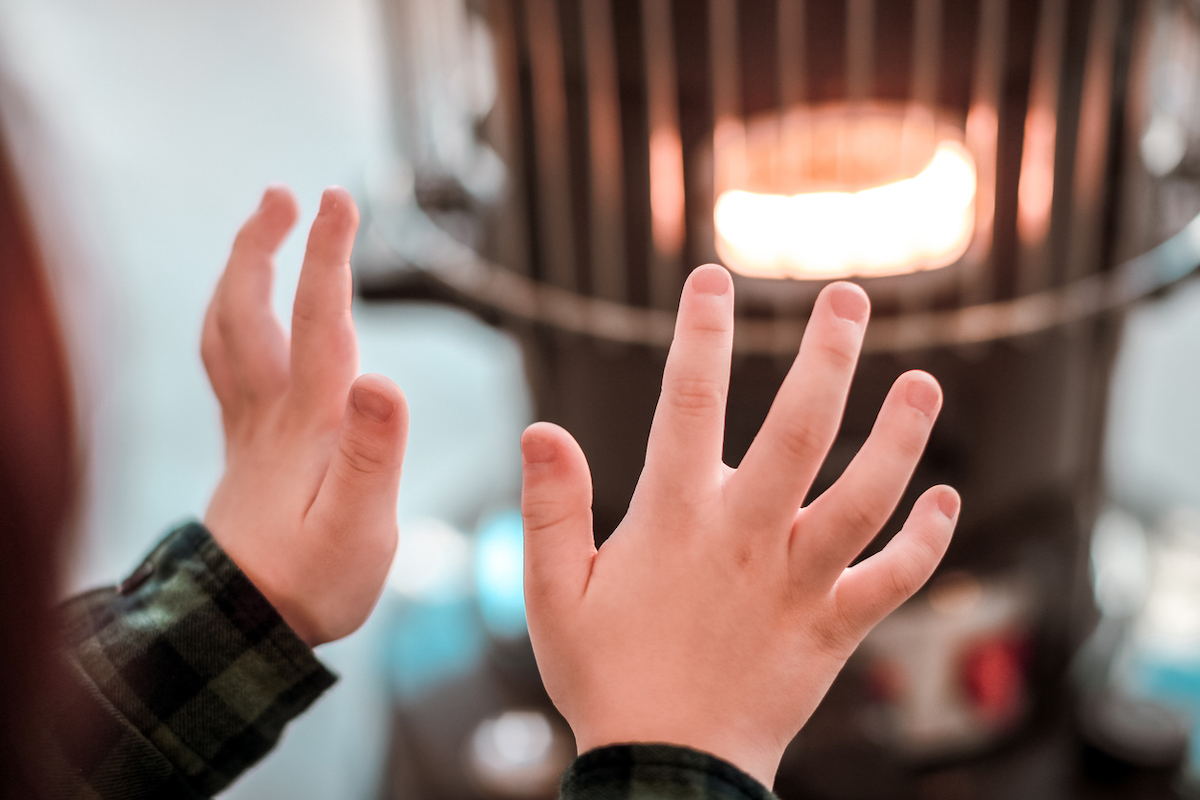 A young boy's hands warming up by heater