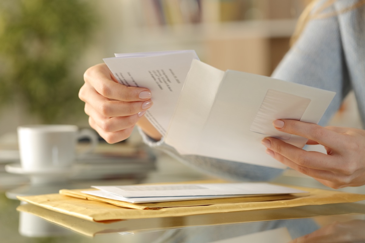 Girl hands opening an envelope on a desk at home