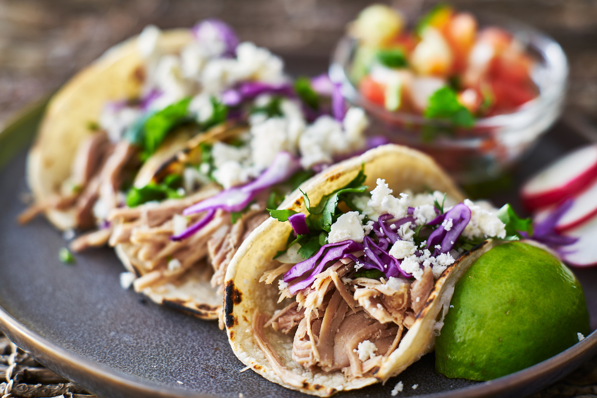 Street tacos with carnitas, red cabbage and queso fresco cheese