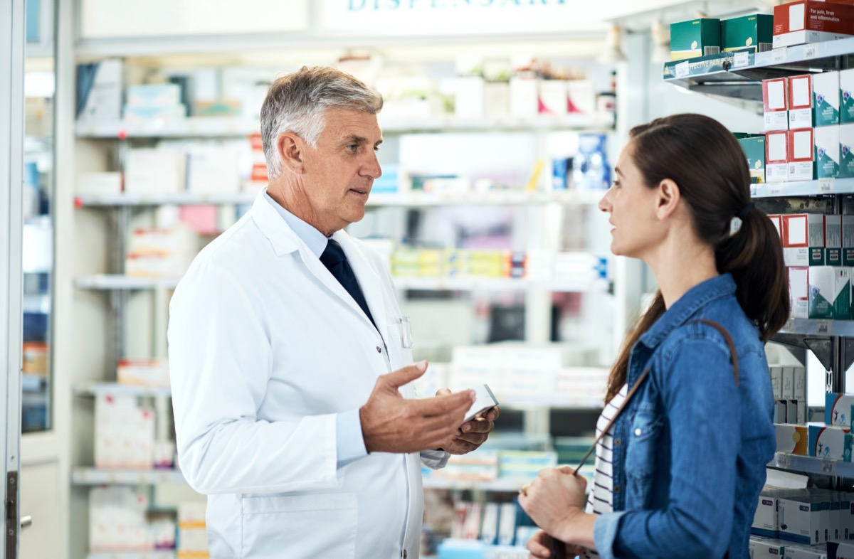 Shot of a mature pharmacist assisting a young woman in a chemist