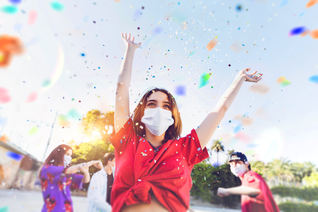 A group of young people wearing face masks celebrate outdoors with confetti