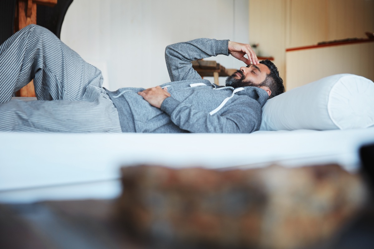 Shot of a mature man lying on his bed feeling exhausted