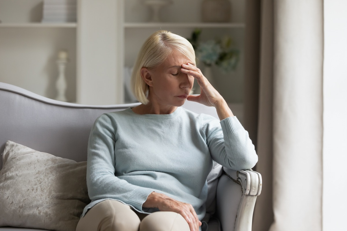 Tired older woman sitting on comfortable sofa in living room, touching forehead. Exhausted mature lady suffering from head ache at home. Unhappy elder grandmother worrying about bad news alone.