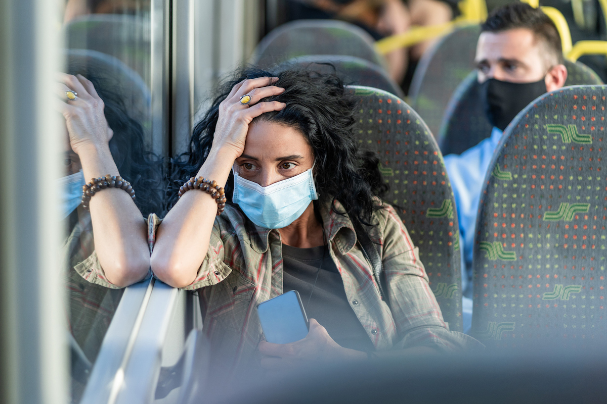 Woman with a protective face mask to avoid infectious diseases, looking tired while traveling by bus