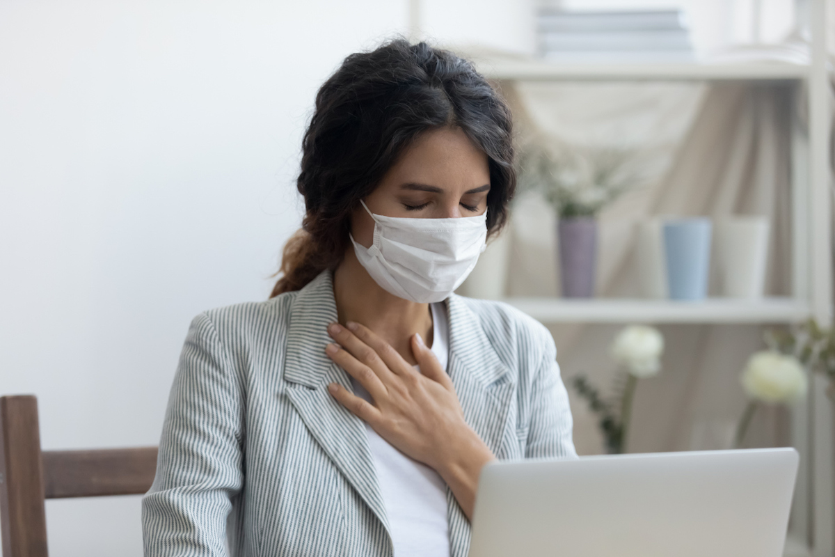Business woman in mask sitting at desk is suffering from repeated coughing and breathing difficulties