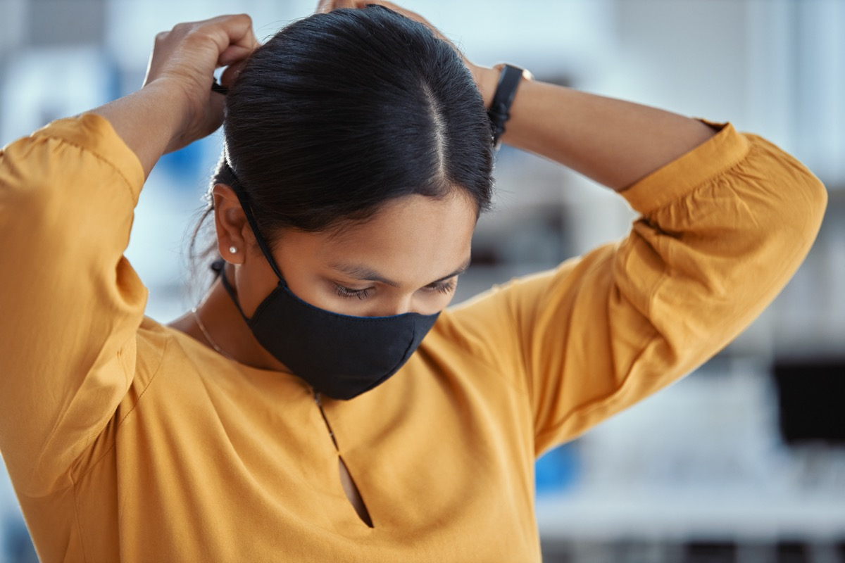 Shot of a young woman putting on a mask in a modern office