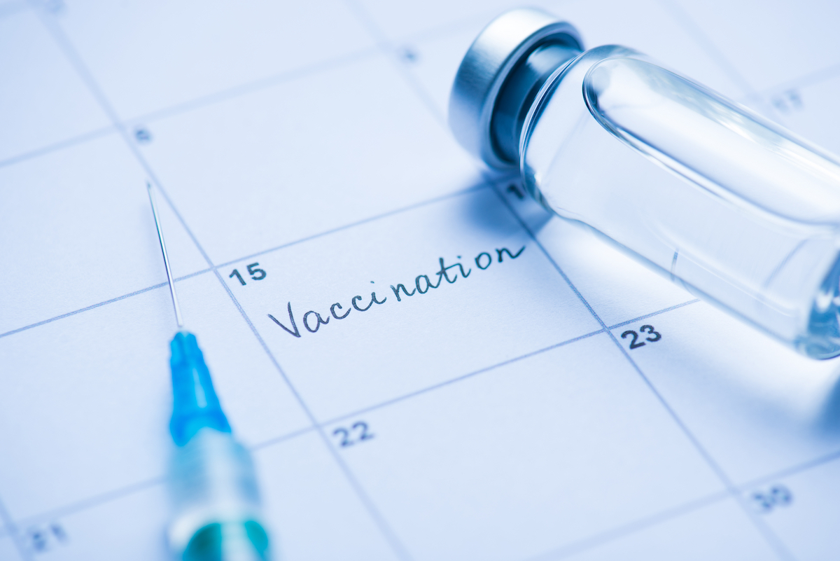 """Close up photo of vial of a vaccine, syringe, and the word """"vaccination"""" written in calendar cell"""
