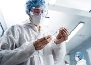young male doctor wearing white gown, holding hypodermic syringe and vaccine in test lap for cure coronavirus for mankind in future.