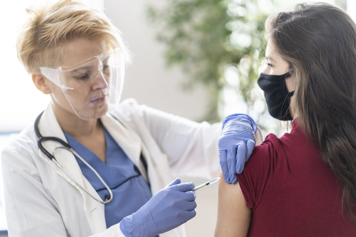 Female doctor vaccinating young woman in her office, wearing a protective face shield