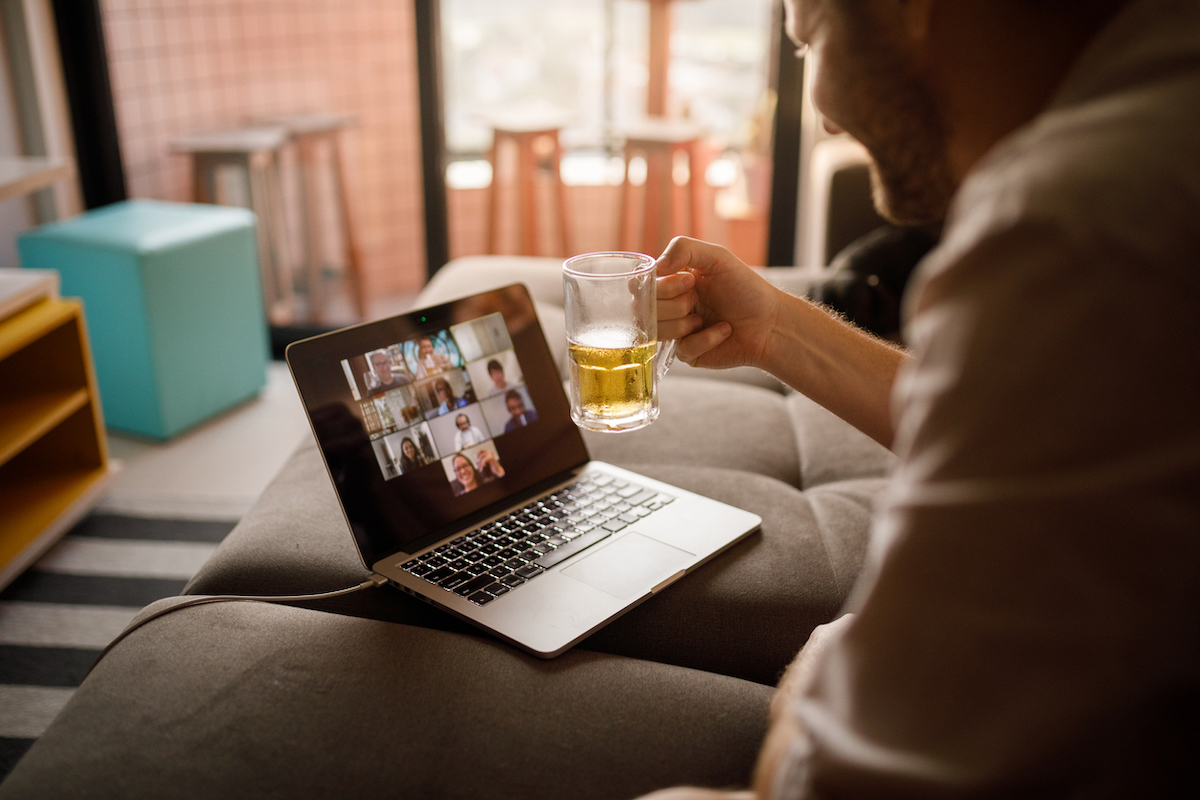 Man hanging out with friends on a video call, potentially celebrating the Super Bowl.