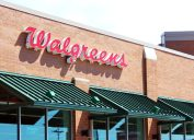 The storefront of a Walgreens pharmacy with red lettering and a green awning