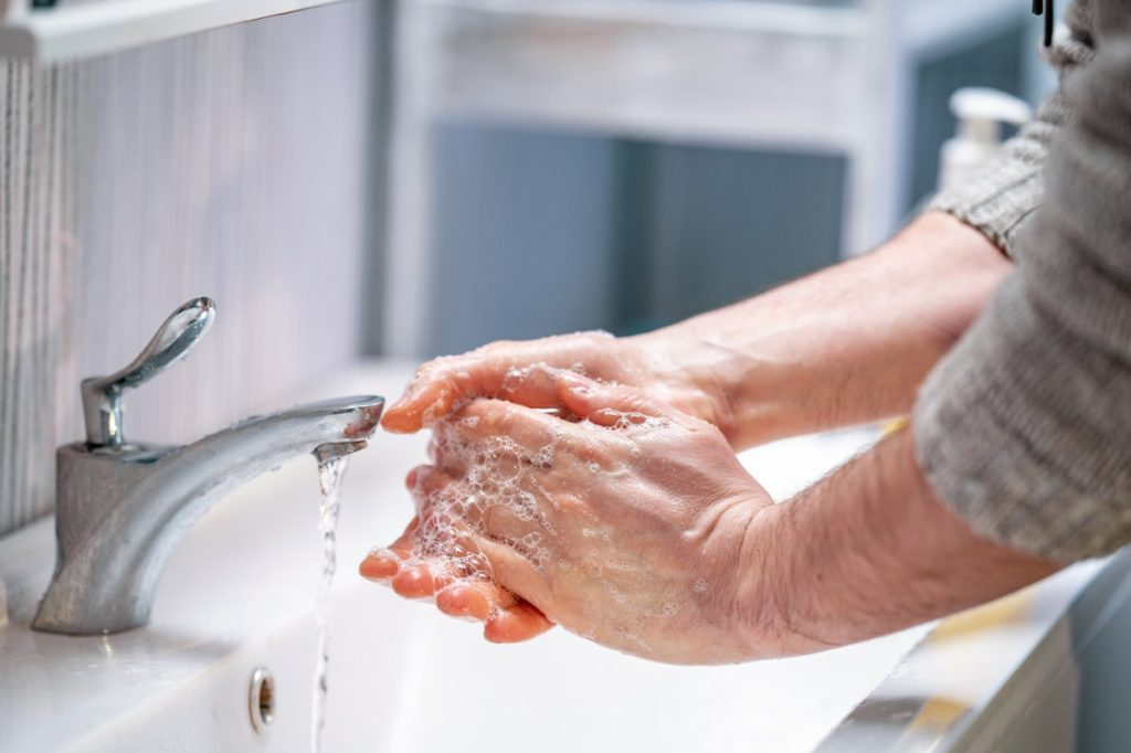 person washing hands at sink