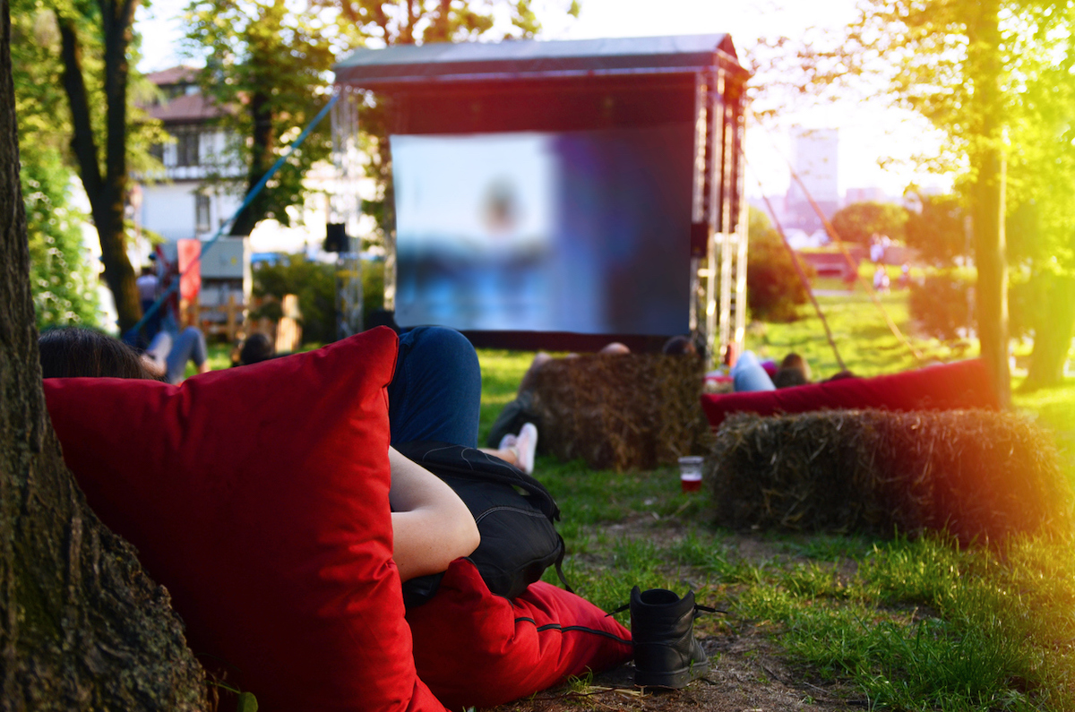 Person laying on red pillows on green Grass looking on big Screen