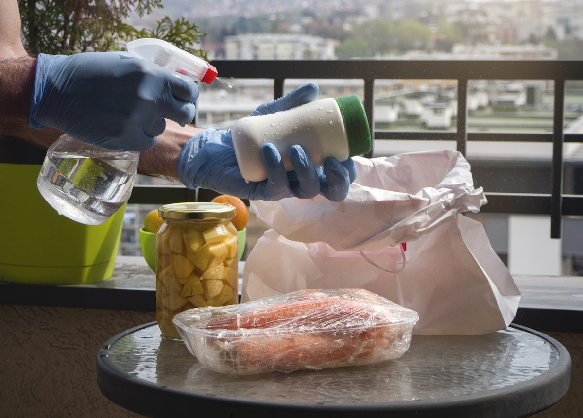 Man wiping down items and groceries with disinfectant or sanitizer spray