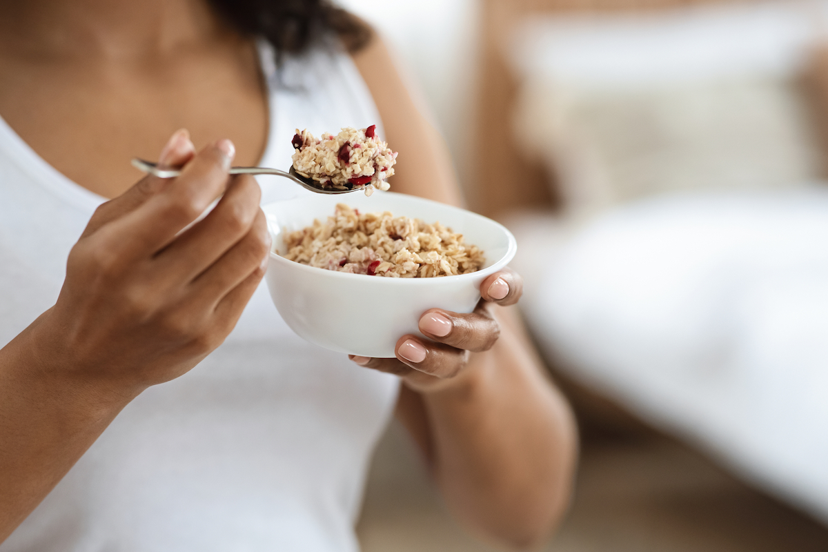 Portrait of woman eating oatmeal with fruits for breakfast