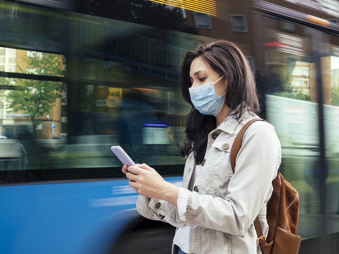 A young woman wearing a face mask checks her smartphone while waiting for a city bus