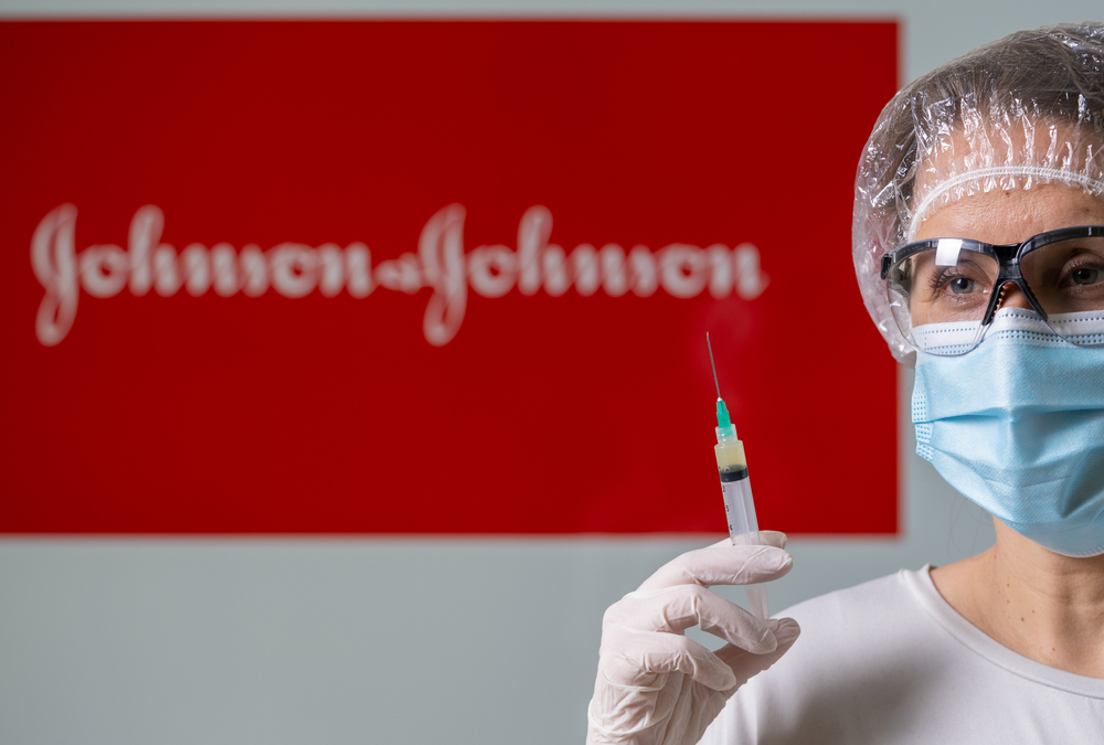 A woman wearing protective glasses, a face mask, and a hair covering holds a syringe in front of a Johnson & Johnson sign