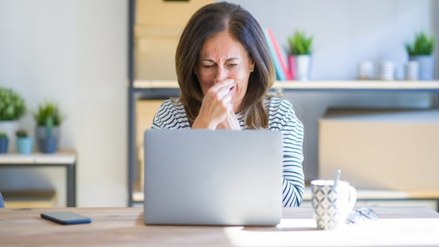 middle aged woman at laptop smelling something terrible