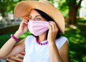 A young woman wearing a large straw hat puts on a pink face mask while standing outdoors