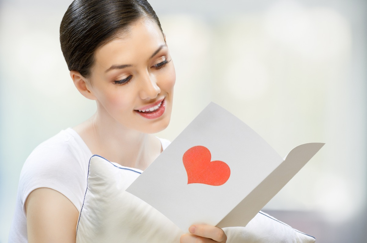 woman holding a card with a heart on it in her hand