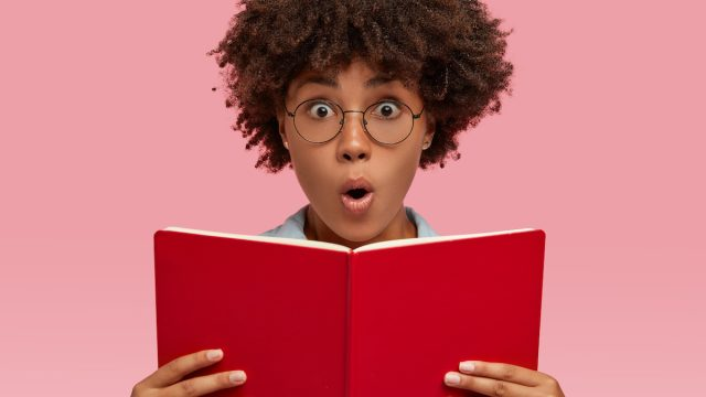 Smart young woman with glasses looking amazed while reading a book
