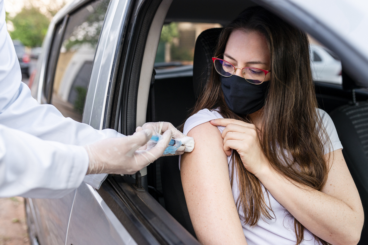 A young woman sitting in a car and wearing a face mask receives the COVID-19 vaccine from a healthcare worker wearing gloves.