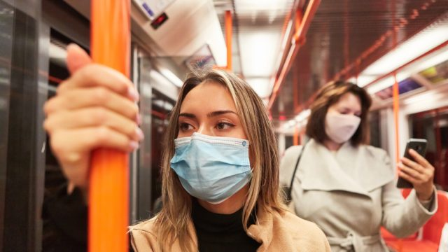 A young woman riding a subway train while wearing a mask, standing in front of another woman who is checking her smartphone