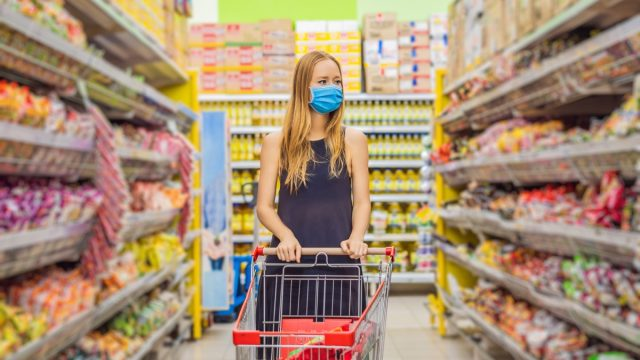 woman with blonde hair pushing grocery cart down snack aisle in supermarket while wearing a mask
