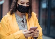 A young woman wearing a yellow jacket and a face mask checks her smartphone.