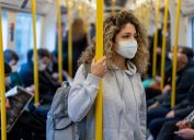 A young woman wearing a face mask riding on public transportation.