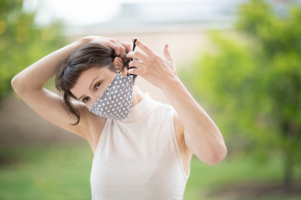 young woman with brown hair putting on cloth face mask