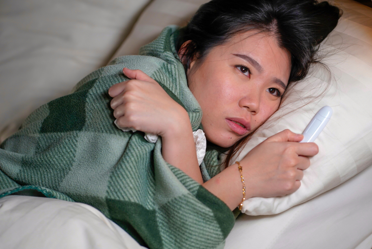 Woman home sick with fever covered in blanket