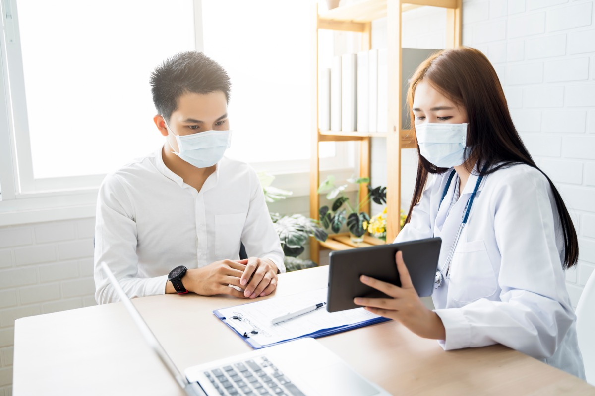 young doctor talking to patient and showing him an ipad