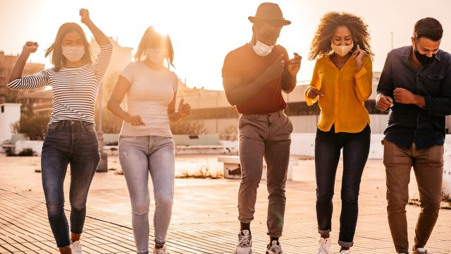 A group of young people wearing face masks dance and celebrate outdoors near sunset.