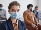 A young person wearing a suit and a face mask sits in front of other coworkers