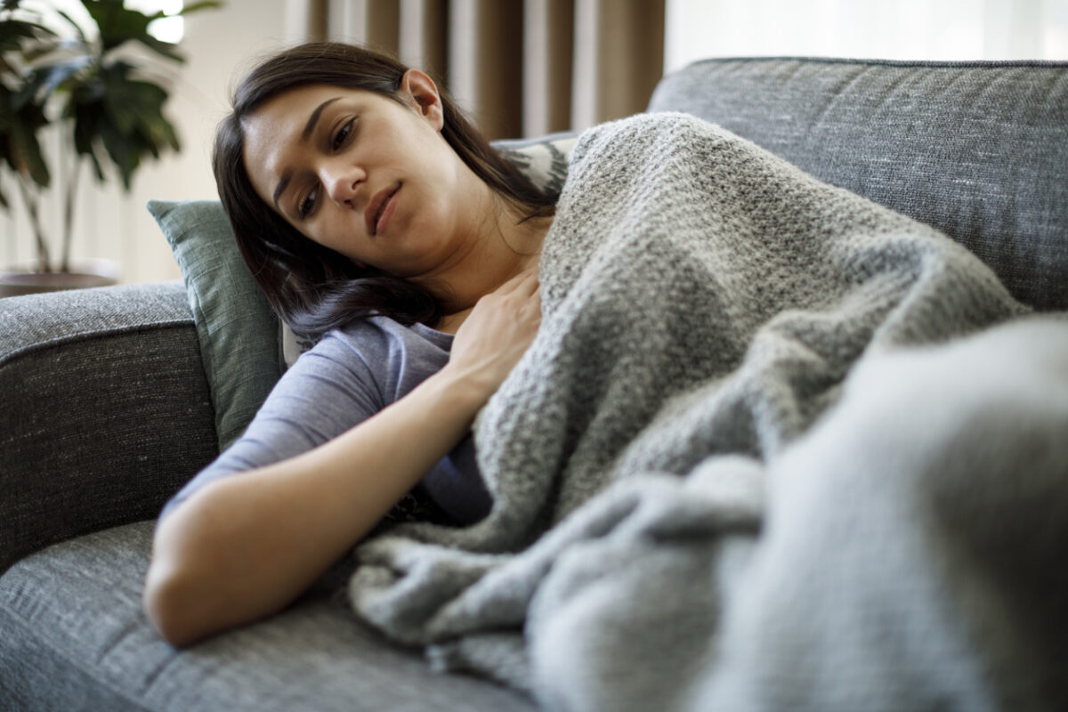 A young woman lies on the couch while covered by a blanket and a tired expression on her face